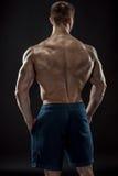Muscular bodybuilder guy doing posing over black background Stock Photos