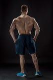 Muscular bodybuilder guy doing posing over black background Stock Photography