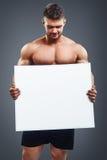 Muscular bodybuilder guy holding blank poster Stock Image