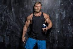 Muscular bodybuilder guy over dark background Royalty Free Stock Image