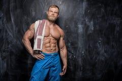 Muscular bodybuilder guy over  dark background. Handsome muscular man bodybuilder posing in the studio on a  dark background Stock Image