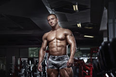 Muscular bodybuilder guy posing in the gym. Muscular bodybuilder guy posing and resting in the gym Royalty Free Stock Photography