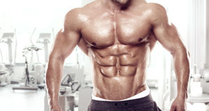 Muscular bodybuilder guy standing on gym. And posing abdominal muscle Stock Photos