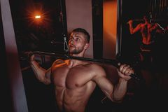 Muscular bodybuilder handsome men doing exercises in gym with naked torso. Strong athletic guy with abdominal muscles and biceps. Muscular bodybuilder handsome Royalty Free Stock Image