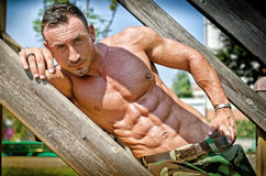Muscular bodybuilder laying on wood stairs on a side Royalty Free Stock Images