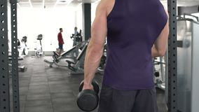 Muscular bodybuilder lifting dumbbells at sport club, active workout in gym. Stock footage stock video