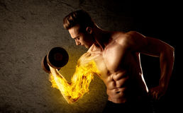 Muscular bodybuilder lifting weight with flaming biceps concept. On background royalty free stock images