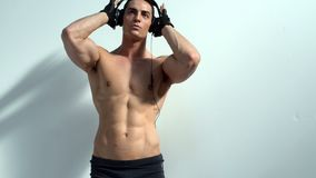 Muscular bodybuilder listening to music with headphones stock video footage