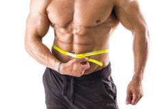 Muscular bodybuilder man measuring belly with tape measure. Muscular bodybuilder man measuring belly and hips with tape measure, close-up isolated on white stock image