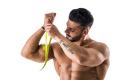 Muscular bodybuilder man measuring thigh with tape measure. Close-up isolated on white background Stock Photo