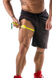 Muscular bodybuilder man measuring thigh with tape measure. Close-up isolated on white background. Unrecognizable person Stock Photo