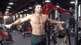 Muscular bodybuilder man with a naked torso doing exercises in gym.  stock video