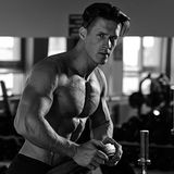 Muscular bodybuilder preparing to exercise in the gym. stock image