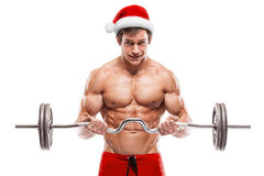 Muscular bodybuilder Santa Claus doing exercises with dumbbells Royalty Free Stock Images