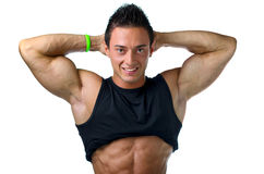 Muscular bodybuilder showing biceps and ripped abs. Muscular young bodybuilder showing biceps and ripped abs, smiling. Isolated on white Stock Photography