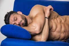 Muscular bodybuilder sleeping on couch royalty free stock images