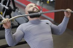 Muscular bodybuilder training in the gym, doing pulldown exercises for muscles. Stock footage Royalty Free Stock Photo