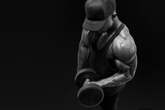 Muscular bodybuilder wearing a  tank top and black cap doing bic. Black and white shot of muscular bodybuilder wearing a  tank top and black cap doing biceps Royalty Free Stock Images