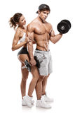 Muscular bodybuilder with woman doing exercises with dumbbells Royalty Free Stock Photography
