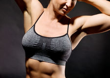 Muscular bodybuilder woman showing her muscles. Muscular bodybuilder woman showing her muscles over black background Royalty Free Stock Photo