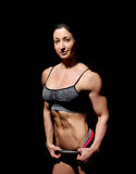 Muscular bodybuilder woman showing her muscles. Royalty Free Stock Photos