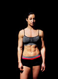 Muscular bodybuilder woman showing her muscles. Muscular bodybuilder woman showing her muscles over black background Stock Images