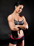 Muscular bodybuilder woman showing her muscles. Muscular bodybuilder woman showing her muscles over black background Royalty Free Stock Photos