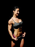 Muscular bodybuilder woman showing her muscles. Stock Photography