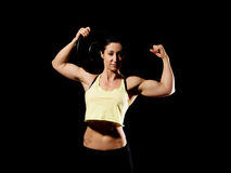 Muscular bodybuilder woman showing her muscles. Muscular bodybuilder woman showing her muscles over black background Royalty Free Stock Image