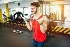 Muscular bodybuilder workout in gym doing biceps exercises. With bar Stock Photo