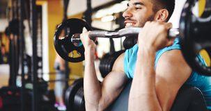 Muscular bodybuilder workout in gym doing biceps exercises. With bar Stock Images