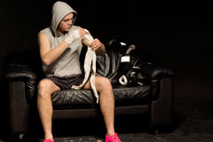 Muscular boxer bandaging his hands Royalty Free Stock Photos