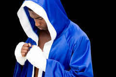 Muscular boxer in in blue hood. Standing over black background Stock Photo