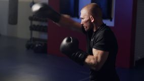 Muscular boxer in boxing gloves making strikes with shadow in gym, slow motion. Low light scene stock video footage