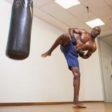 Muscular boxer kicking punching bag in gym Stock Images