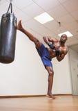 Muscular boxer kicking punching bag in gym Royalty Free Stock Photo