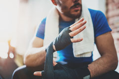 Muscular Boxer man prepairing hands for hard kickboxing training session in gym.Bearded Young athlete tying black boxing stock image