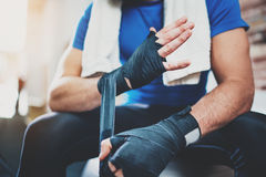 Muscular Boxer man prepairing hands for hard kickboxing training session in gym. Young athlete tying black boxing. Closeup view on male hands of young athlete Stock Photos