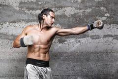 Muscular boxer man punching. Side view of muscular boxer man punching Stock Photo