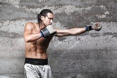 Muscular boxer man punching. Side view of muscular boxer man punching Royalty Free Stock Photo