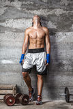 Muscular boxer man standing on the wall. Portrait of muscular boxer man standing on the wall and looking up Royalty Free Stock Image