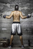 Muscular boxer man standing on the wall. Rear view of muscular boxer man standing on the wall Royalty Free Stock Images