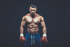 Muscular boxer in studio shooting, on black background. Muscular boxer in studio shooting, on black background Stock Photo