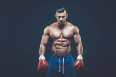 Muscular boxer in studio shooting, on black background. Muscular boxer in studio shooting, on black background Royalty Free Stock Images