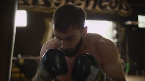 Muscular boxer training with punching bag. Boxing man training in slow motion stock video footage