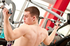 Muscular boy trains in fitness club Royalty Free Stock Photos