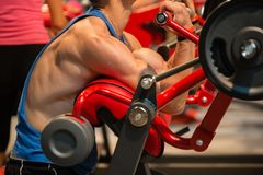 Muscular Boy: Workout at Gym with Red Equipment for Biceps.  Stock Photography