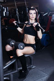 Muscular brunette fitness girl doing exercises in the gym. Fitness girl lifting weights on a machine for bodybuilders. Royalty Free Stock Image
