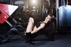 Muscular brunette fitness girl flexing muscles on leg press machine in the gym. Fitness girl lifting weights on a machine. Royalty Free Stock Photo