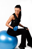 Muscular brunette sitting on fitness ball Royalty Free Stock Photos